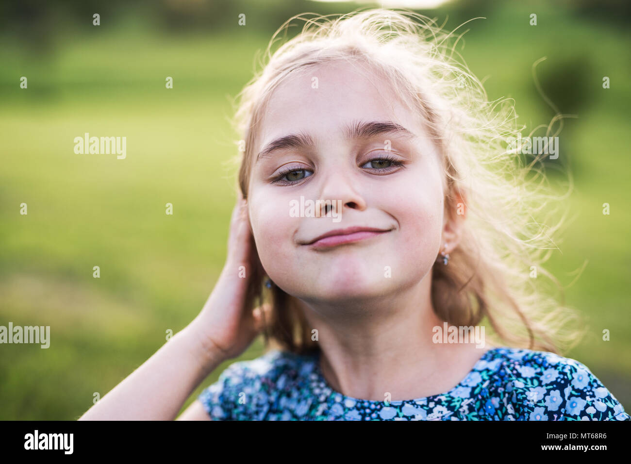 A small girl in the garden in spring nature. - Stock Image