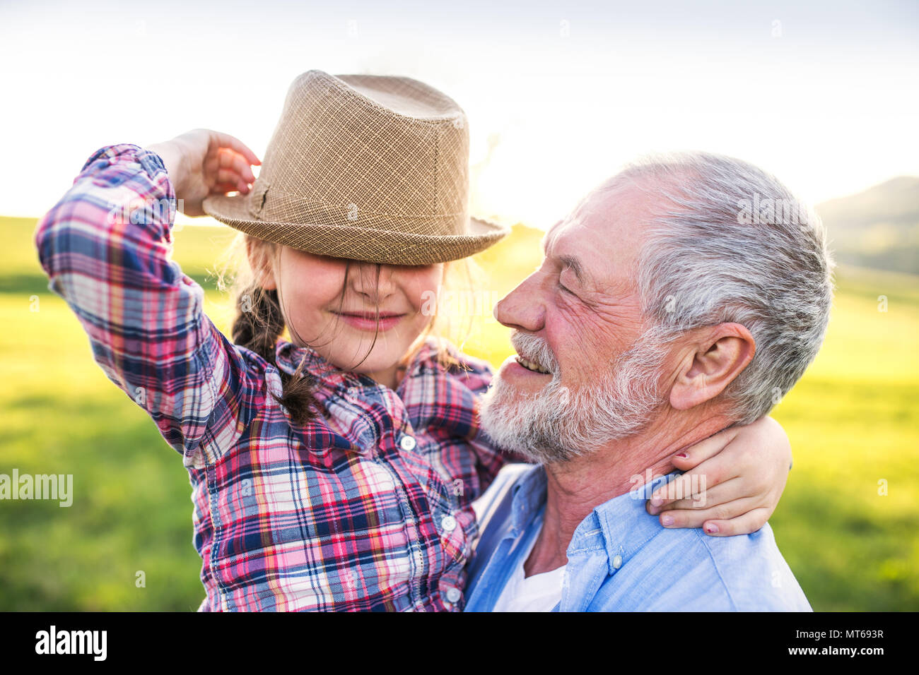 A small girl with grandfather outside in spring nature, having fun. - Stock Image
