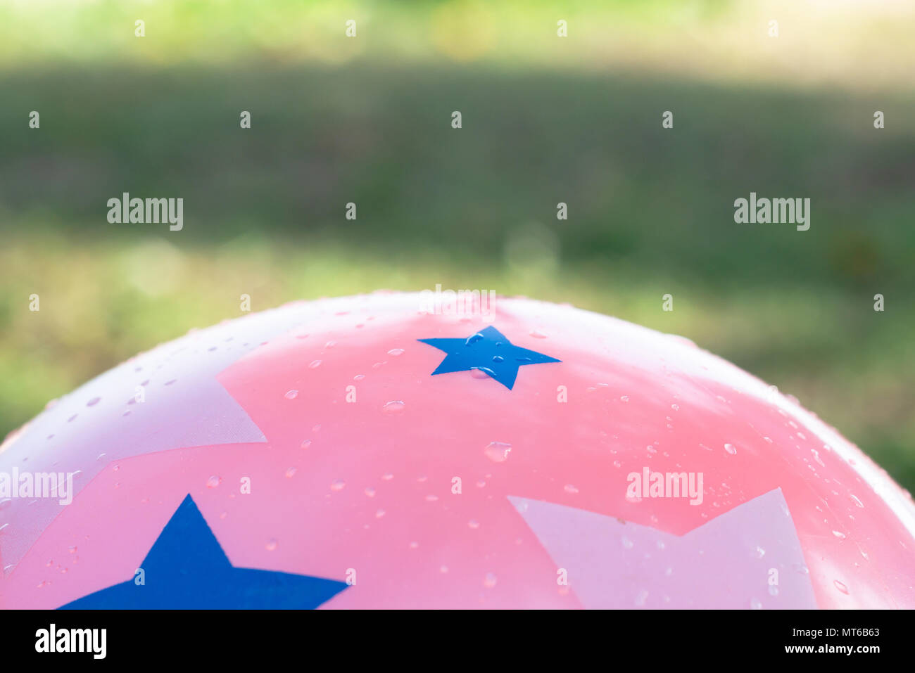 Wet pink ball and abtract background of green nature - Stock Image