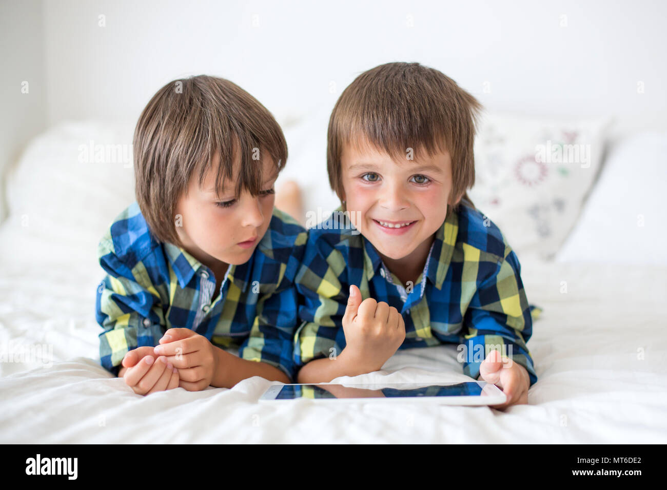 Two preschool children, boy brothers, playing at home in bed on tablet - Stock Image