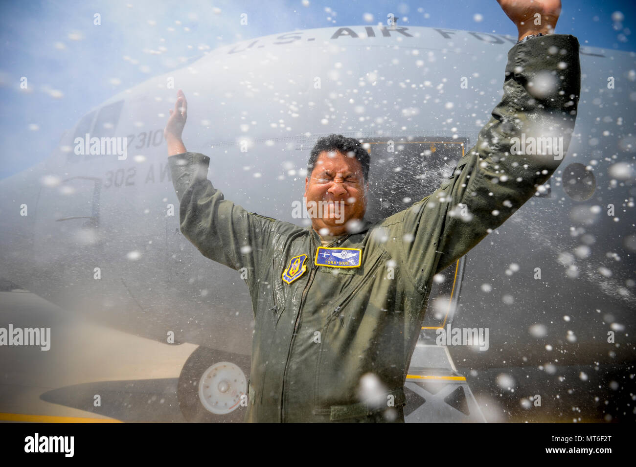 Air Force Reserve Lt. Col. Tora Gore, a C-130 flight test navigator with the 339th Flight Test Squadron, receives showers of water and champaign after flying his last mission before retirement July 20, 2017, at Robins Air Force Base, Ga. Gore completed 10 years of Air Force active-duty service before joining the Alaska Air National Guard in 2004 and the Air Force Reserve in 2008. (U.S. Air Force photo by Jamal D. Sutter) - Stock Image