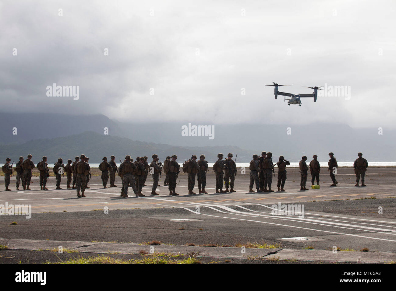 U.S. Marines with India Company, 3rd Battalion, 3rd Marine Regiment, standby for a MV-22 Osprey aircraft with Marine Medium Tiltrotor Squadron 268, prior to conducting a non-combatant evacuation operation (NEO) aboard Marine Corps Air Station Kaneohe Bay, July 25, 2017. During a NEO, Marines provide security, evacuate civilians, establish an intermediate support base and operate from naval support platforms at sea. Military personnel with Marine Aircraft Group 24 and 3rd Marines worked together in conducting a NEO which took place at three training areas across Oahu to include Marine Corps Tra Stock Photo