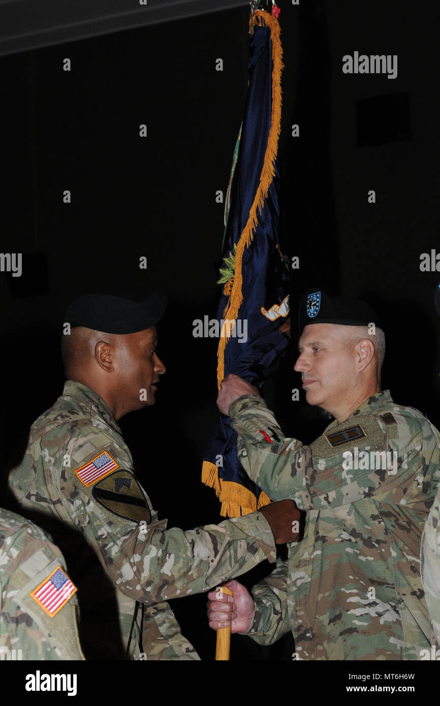 Col. Flint Patterson, commander of the 4th Cavalry Multi-Functional Training Brigade, hands Lt. Col. Fred Grospin, the commander of the 3rd Battalion, 337th Regiment, the unit colors during a change of command ceremony June 4 at Waybur Theatre on Fort Knox, Kentucky. The passing of the unit colors represents the transfer of authority and responsibility for the unit from one commander to another. (Photo by Army Sgt. Rakeem Carter/Released.) - Stock Image