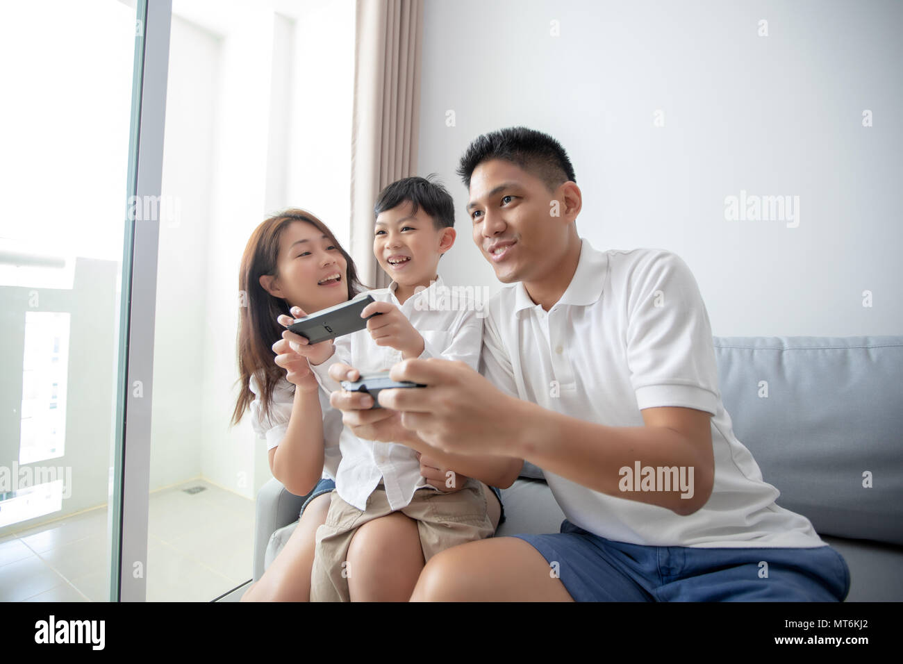 Asian family having fun playing computer console games together, Father and son have the handset controllers and the mother is cheering the players. - Stock Image