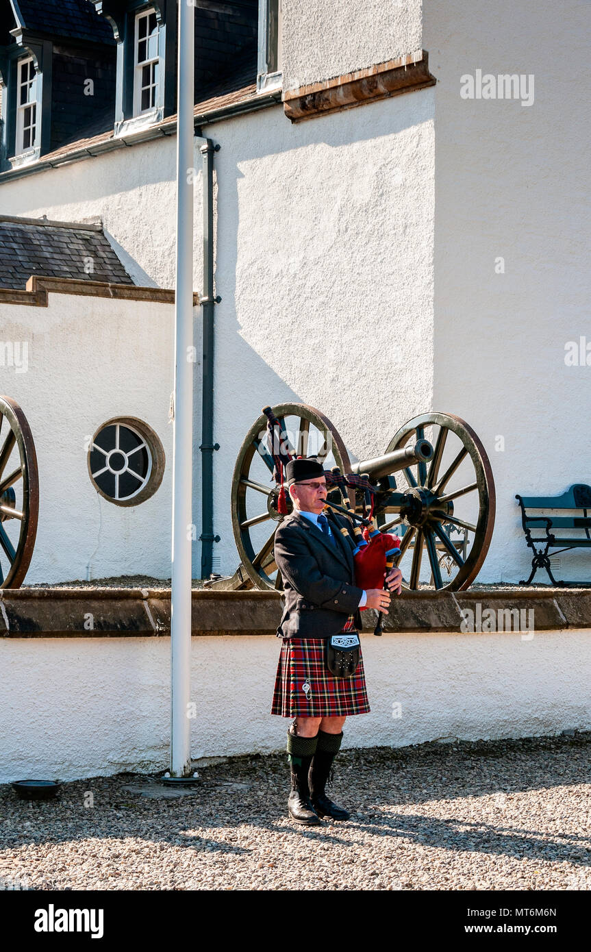 A Scottish piper in traditional highland dress plays typical airs on the bagpipes standing before a wall outside the tall white façade of Blair Castle - Stock Image