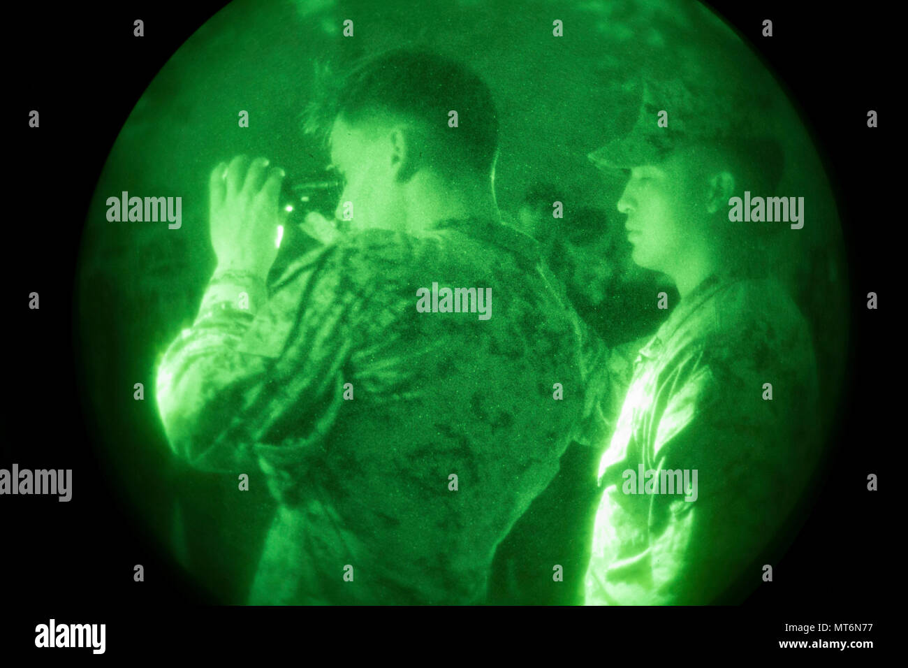 U.S. Marine Corps Sgt. Pawel Cabaj, left, bust instructor, 2nd Marine Division, demonstrates how to use a PVS-14 night vision device during Career Orientated Training for Midshipmen (CORTRAMID) Marine Week, Camp Lejeune, N.C., July 25, 2017. The purpose of CORTRAMID is to expose students to opportunities in the Fleet Marine Forces and generate an interest in a Marine Corps commission. (U.S. Marine Corps photo by Lance Cpl. Ashley D. Gomez) Stock Photo