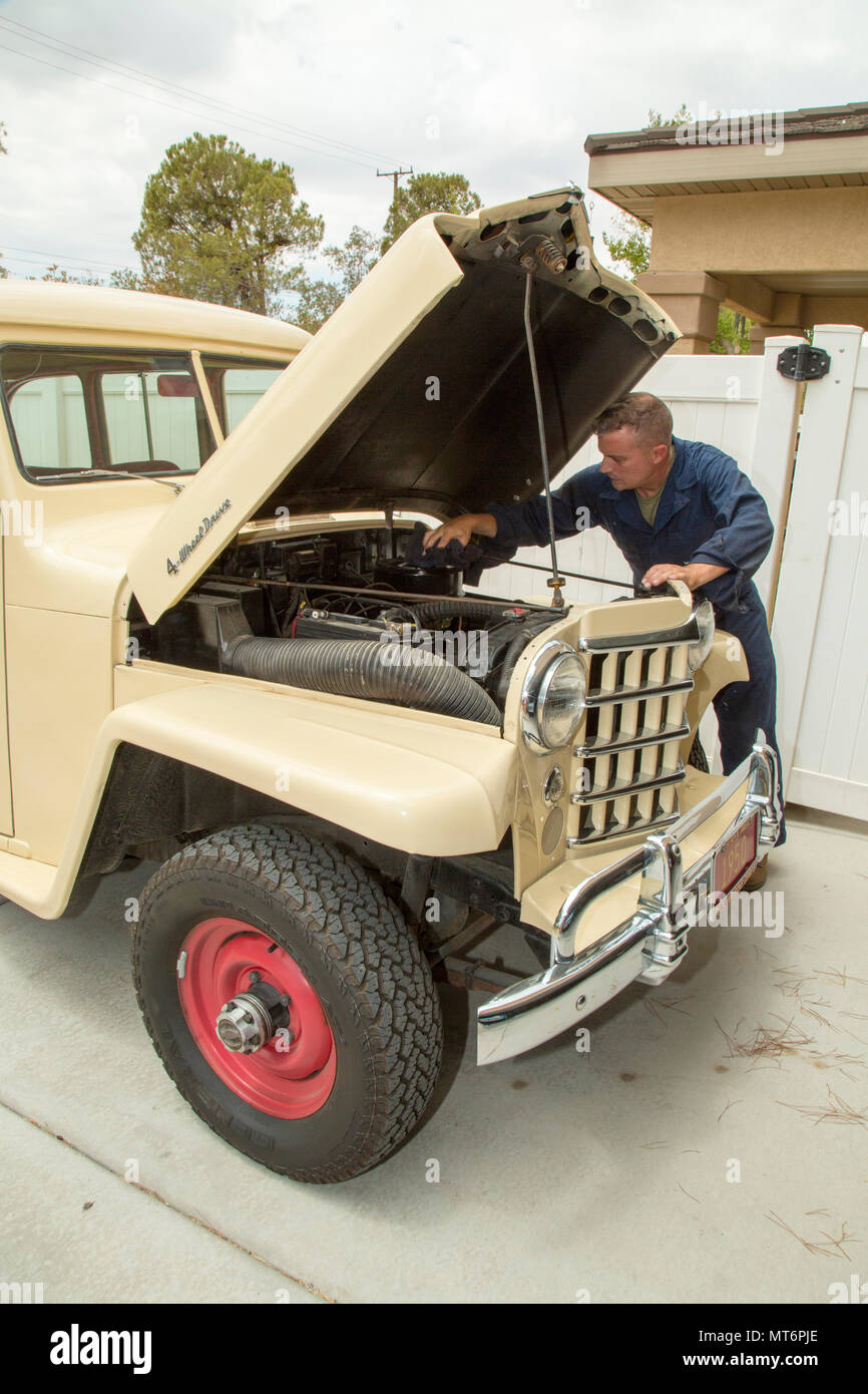 Lieutenant Colonel Timothy Silkowski, director of Fleet Support Division, adjusts the intake manifold on the carburator of his 1950 Jeep Willys Station Wagon, aboard Marine Corps Logistics Base Barstow, Calif., July 25. He found the vehicle abandoned and burried up to the wheel wells in sand, and has worked diligently to restore it in his free time. Stock Photo