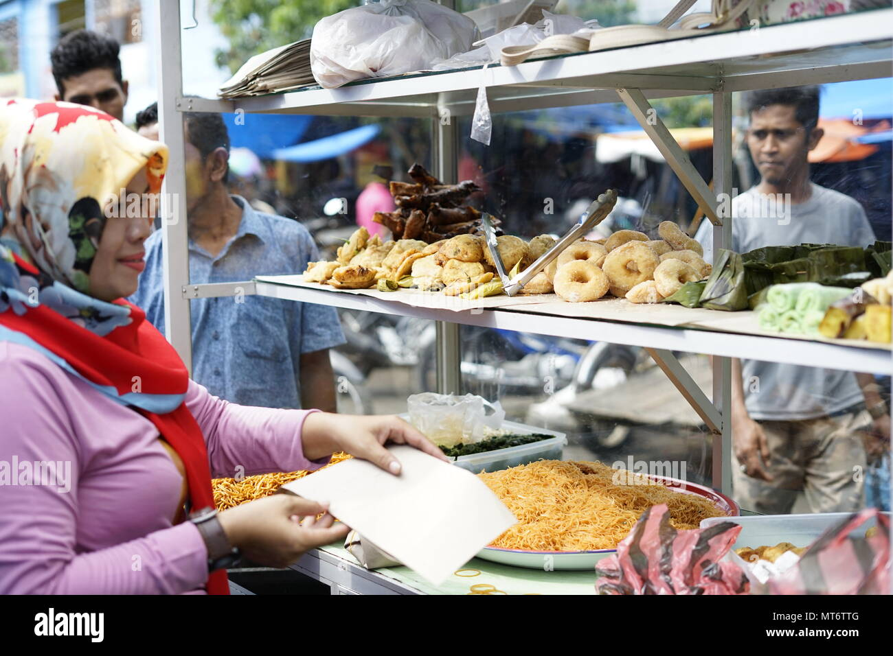 Muslim shoppers buying food from street vendor for breaking fast or iftar in Banda Aceh Stock Photo