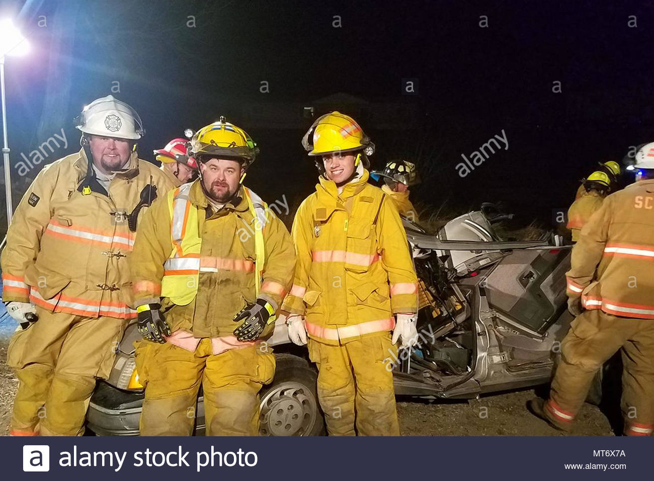 Sean Baker, middle, volunteer firefighter and aircrew flight equipment mechanic for M1 support services at the 40th Helicopter Squadron, poses for a photo after extraction training Mar. 21, 2017, at the Sand Coulee Volunteer Fire Department, Mont. Baker has been a volunteer firefighter for 18 years and was voted in as member of the SCFD in November 2016. (Courtesy photo) - Stock Image