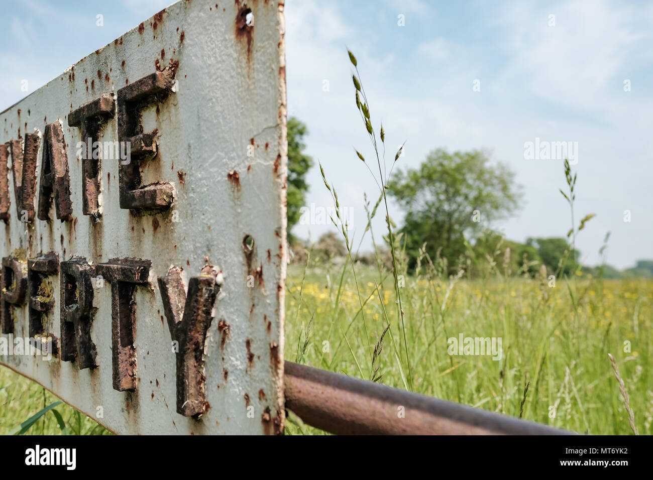 Close-up, abstract image of part of a metal Private Property sign attached to a locked farm gate.  Meadow grass can be seen in the background. Stock Photo