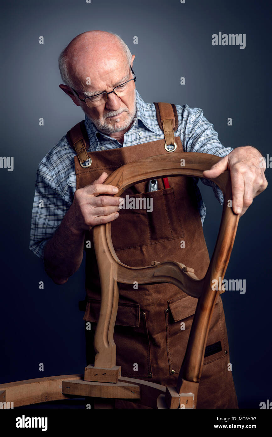 senior caucasian craftsman check unfinished chair studio shot - Stock Image