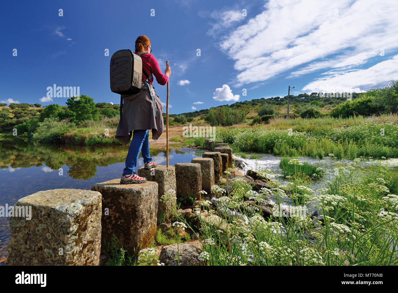 Woman with walking stick crossing stepping stones through river Ponsul - Stock Image