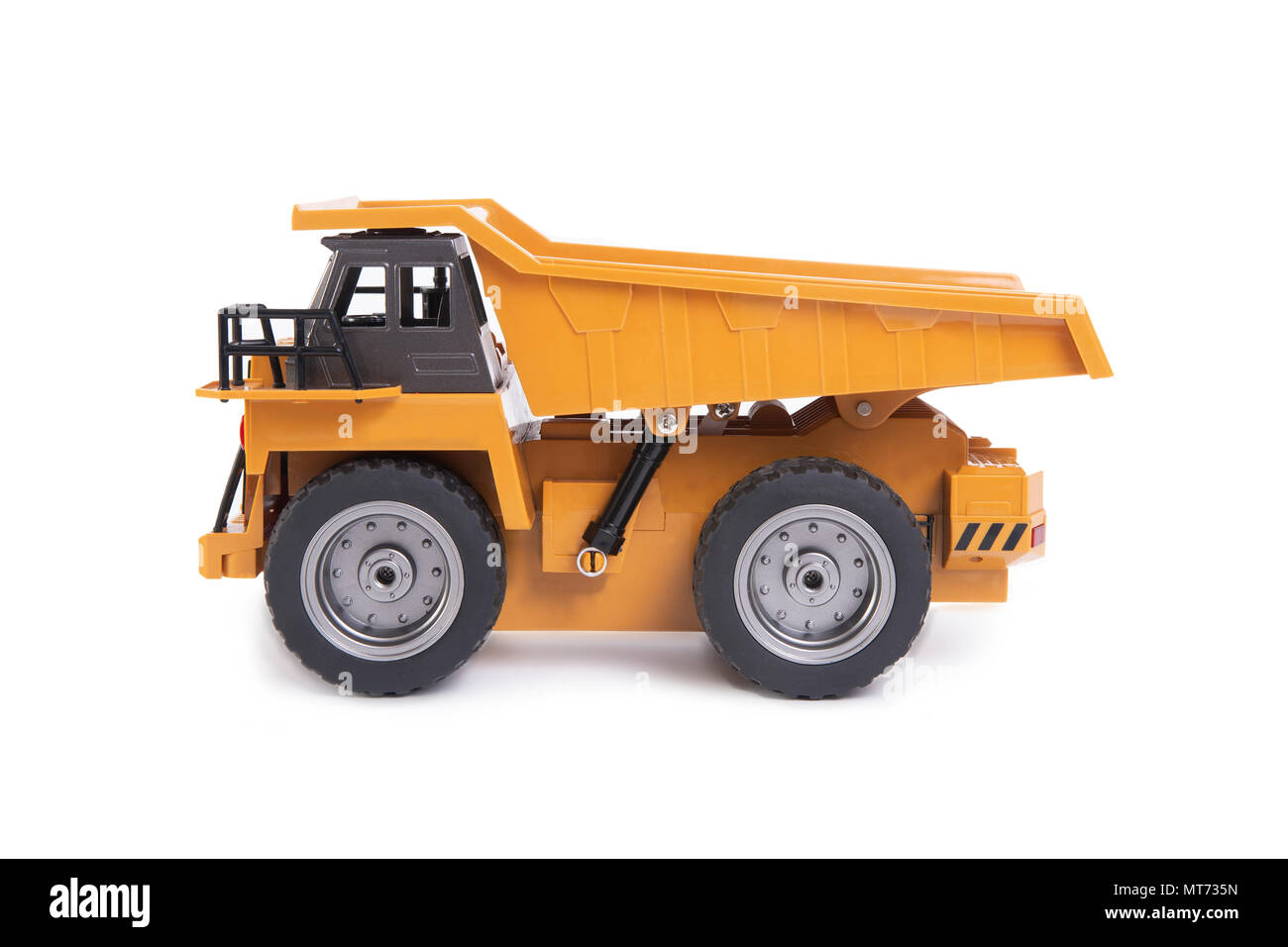 Side view of yellow truck toy model on white background. - Stock Image