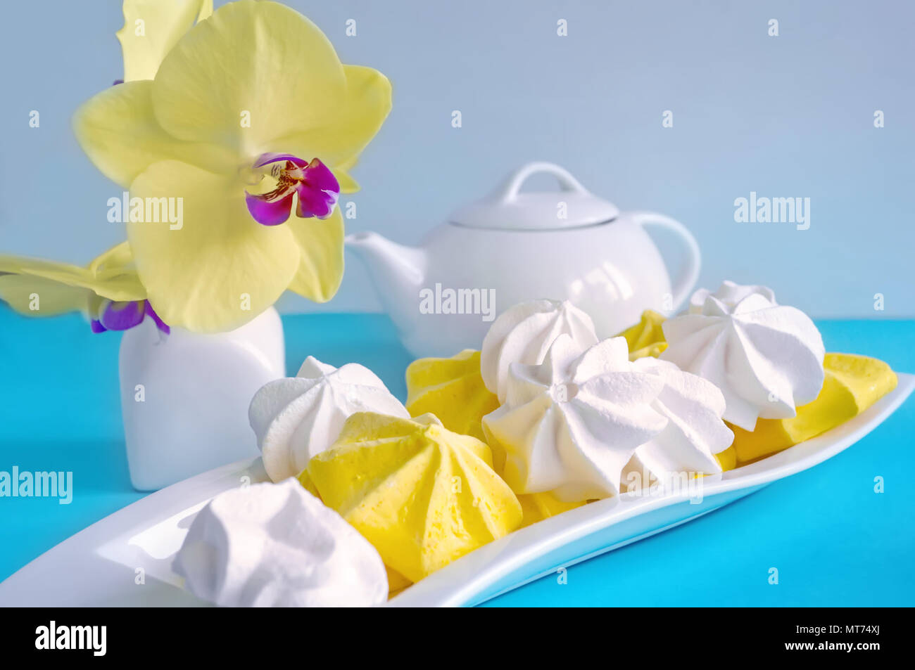 White and yellow meringue on blue background in tea serving with white kettle Stock Photo