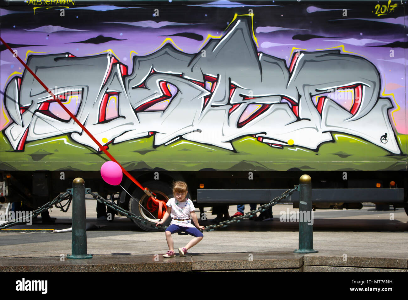 ZAGREB, CROATIA - MAY 19, 2018 : A little girl with balloon sitting on an iron chain fence of Mandusevac fountain in front of a truck painted with gra Stock Photo