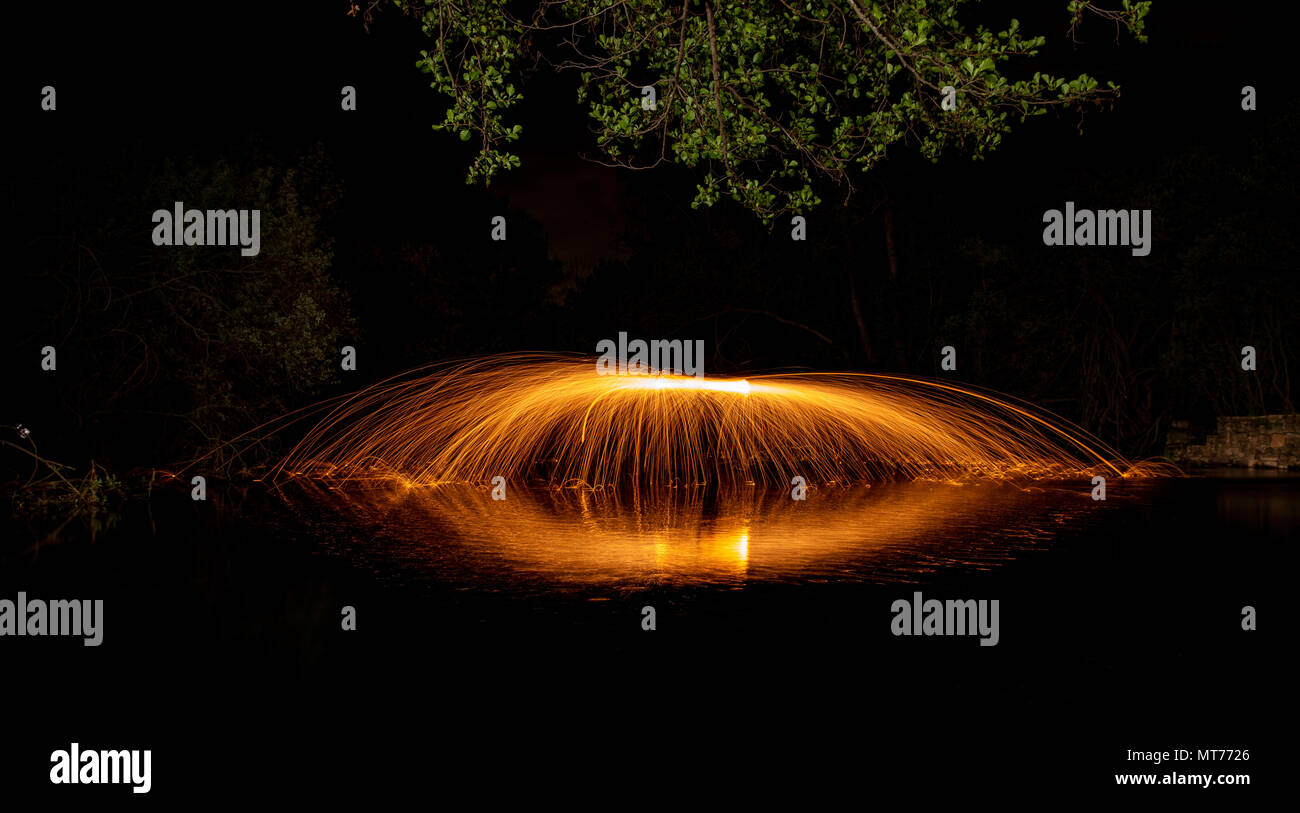 long exposure with sparks of steel wool on a stream of water and reflections Stock Photo