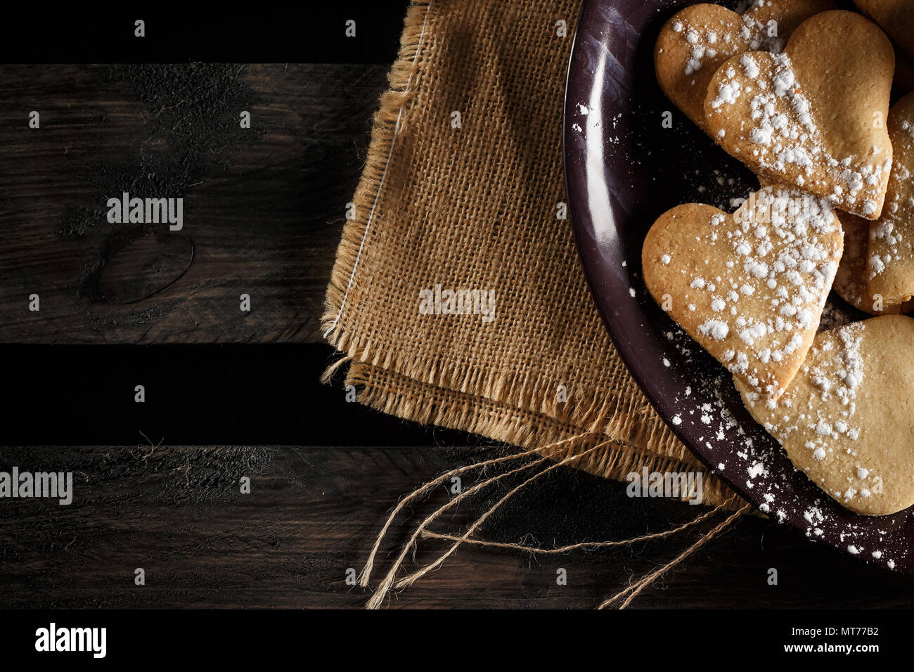 Delicious home-made heart-shaped cookies sprinkled with icing sugar on sackcloth and wooden boards. Horizontal image seen from above. - Stock Image