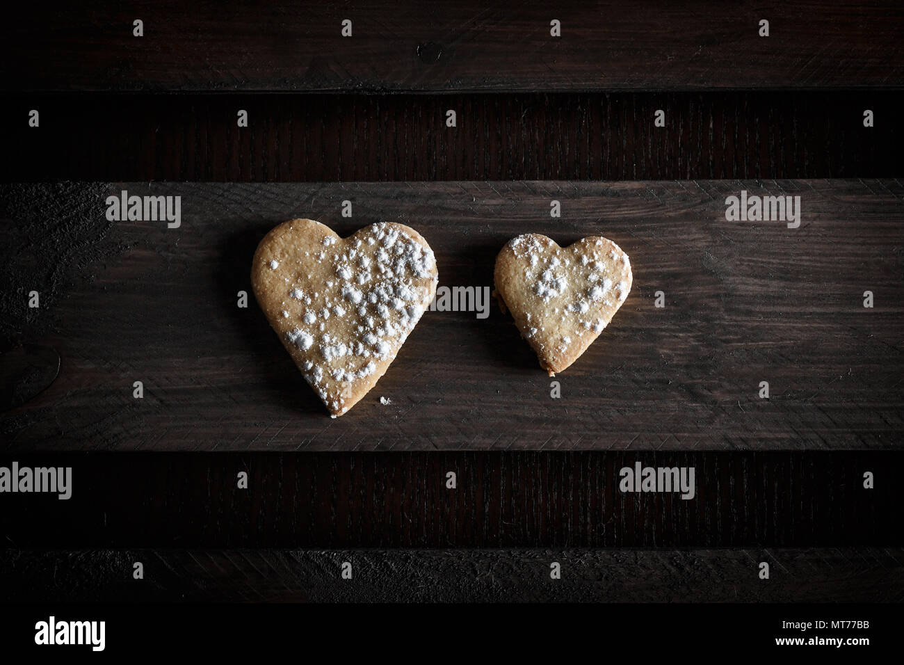 Two delicious home-made heart-shaped cookies sprinkled with icing sugar in a wooden board. Horizontal image seen from above. Concept of love in couple Stock Photo