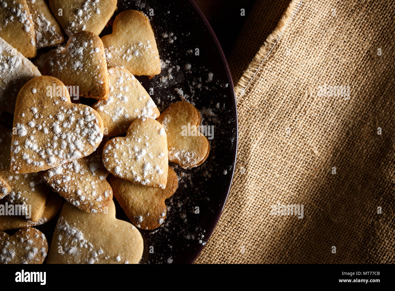 Delicious home-made heart-shaped cookies sprinkled with icing sugar on sackcloth and wooden boards. Horizontal image seen from above. Stock Photo