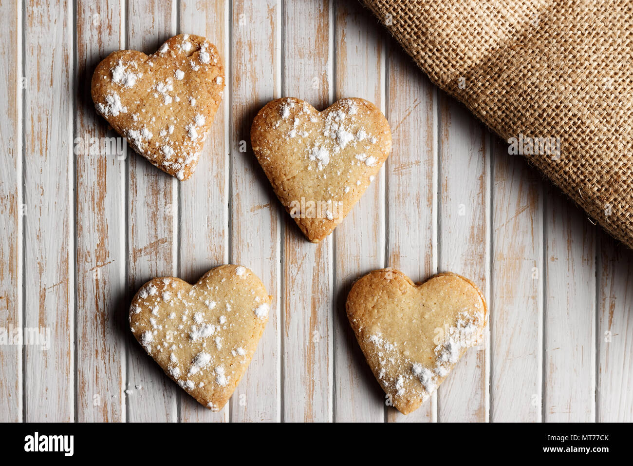 Delicious home-made heart-shaped cookies sprinkled with icing sugar in a wooden board. Horizontal image seen from above. - Stock Image