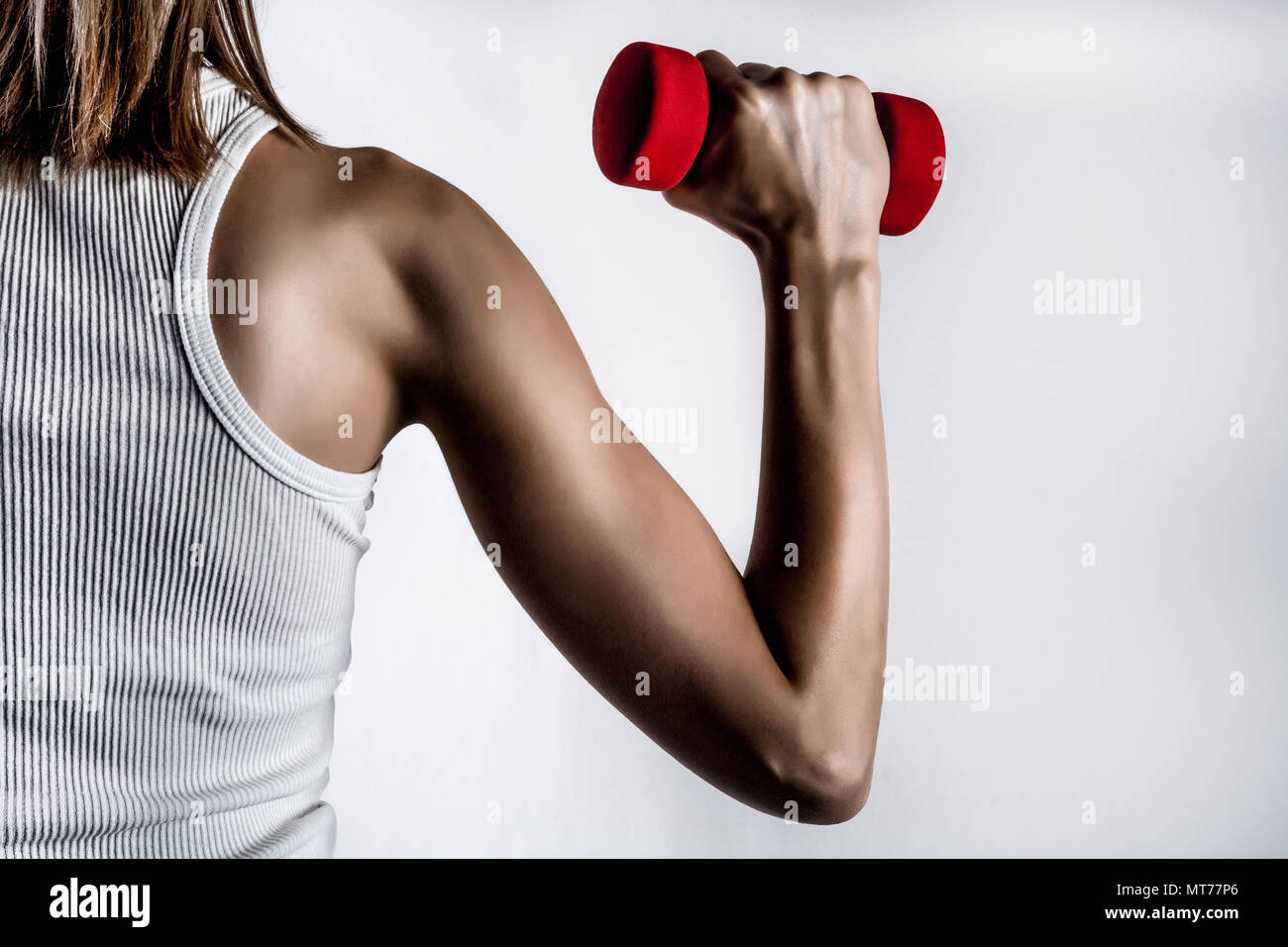 Female back and muscle hand with dumbbell in t shirt in gray studio background and shadow. Biceps curl and Sport, fitness concept Stock Photo