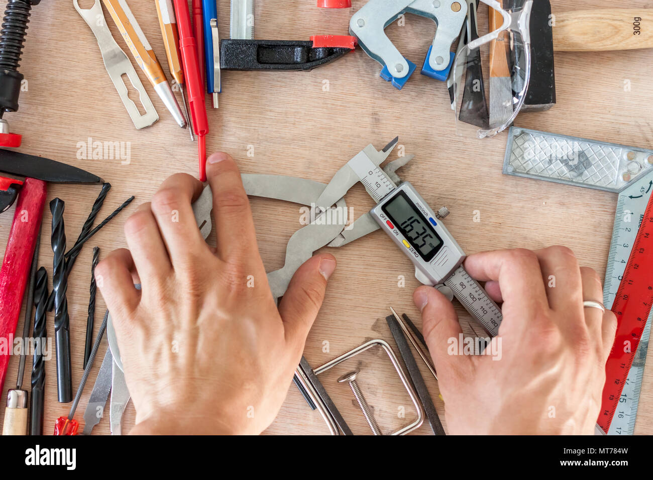 man measuting part with calipers in workshop - Stock Image