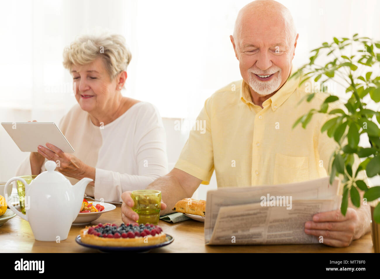 Happy elderly woman using a tablet and her husband reading a newspaper Stock Photo