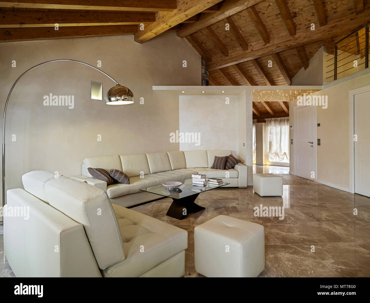 living room interior in foreground the beige leather sofa and the glass coffee table with arch floor lamp the ceiling is made of wooden beams exposed - Stock Image