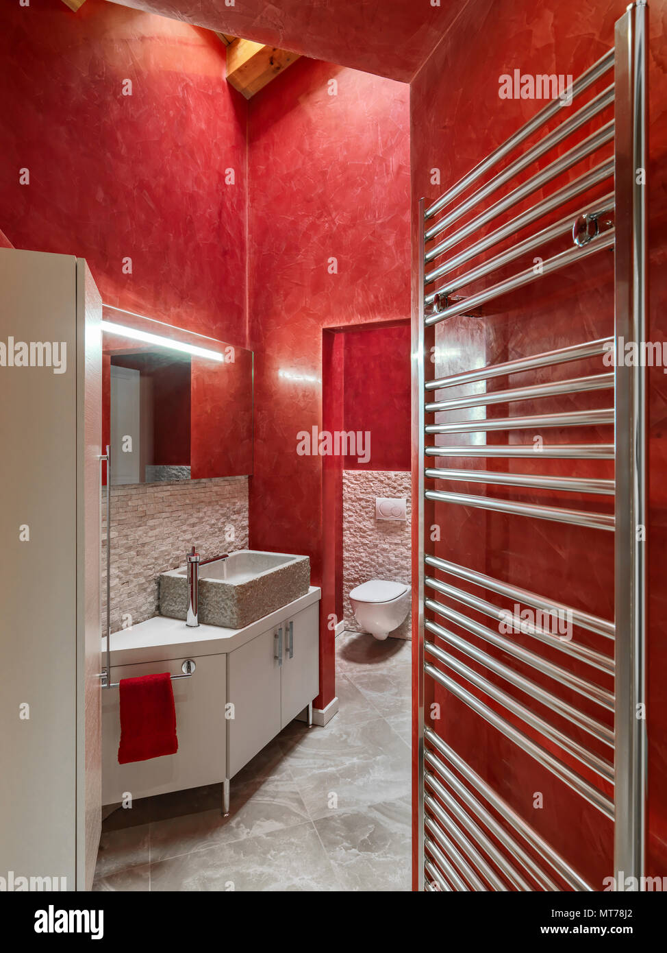 modern bathroom interior with red wall, in the foreground the wooden cabinet with stone countertop washbasin and chrome radiator annd wood floor - Stock Image