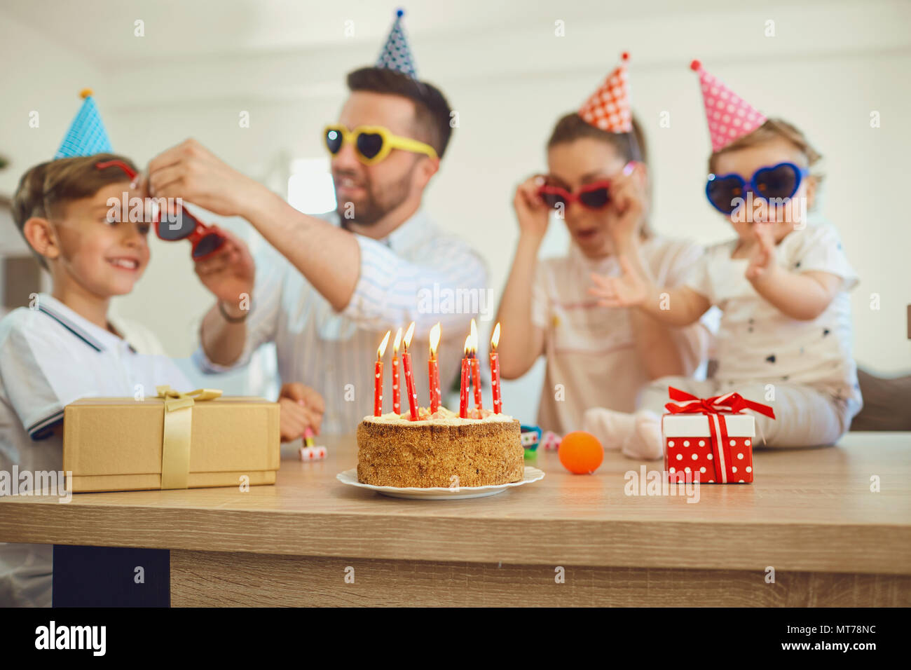 Birthday cake with candles and family out of focus. - Stock Image