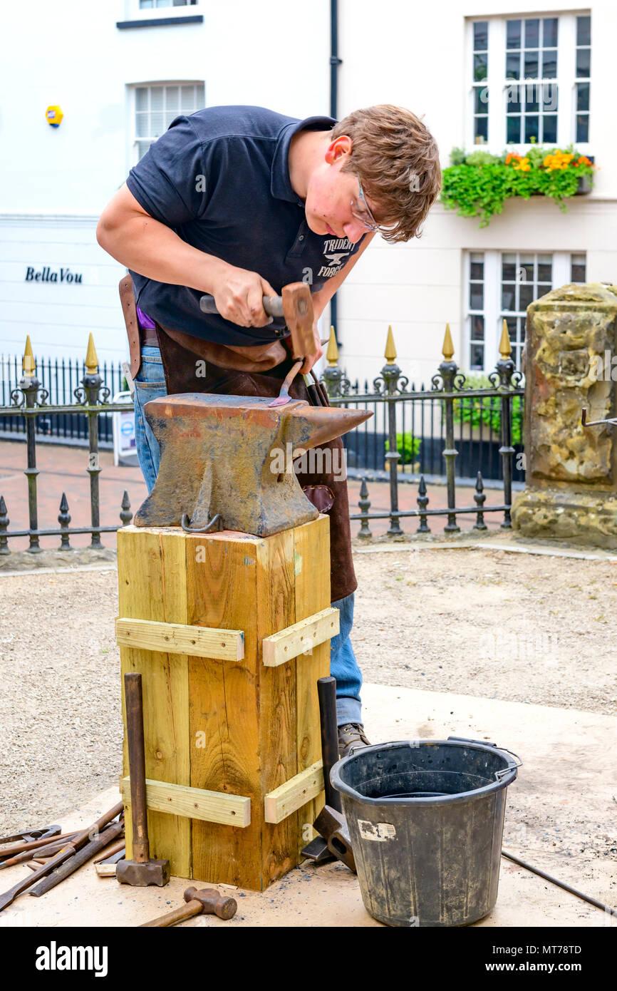 blacksmith working outdoors at the pantiles tunbridge wells making tradition iron items - Stock Image