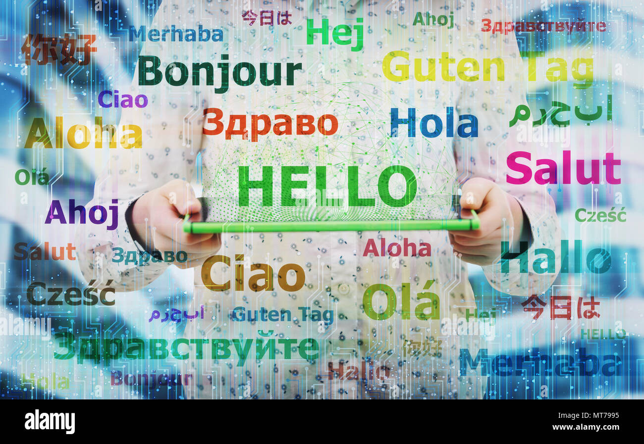 Young woman holding electronic tablet showing the word hello in different languages. Learning and speaking many languages easier using modern technolo - Stock Image