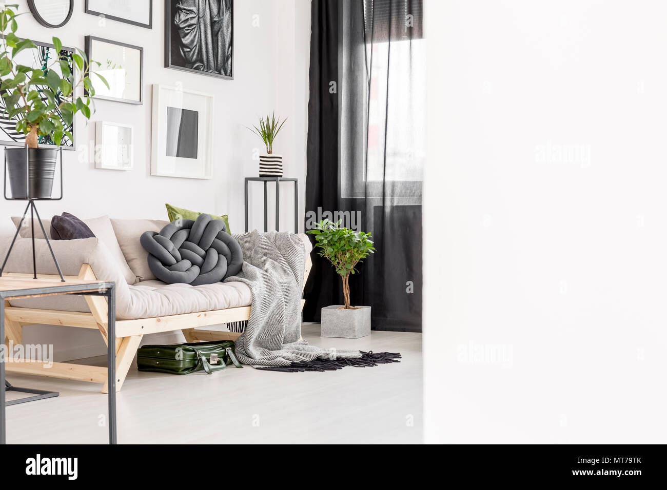 Beige futon in bright living room interior with plant, posters and ...
