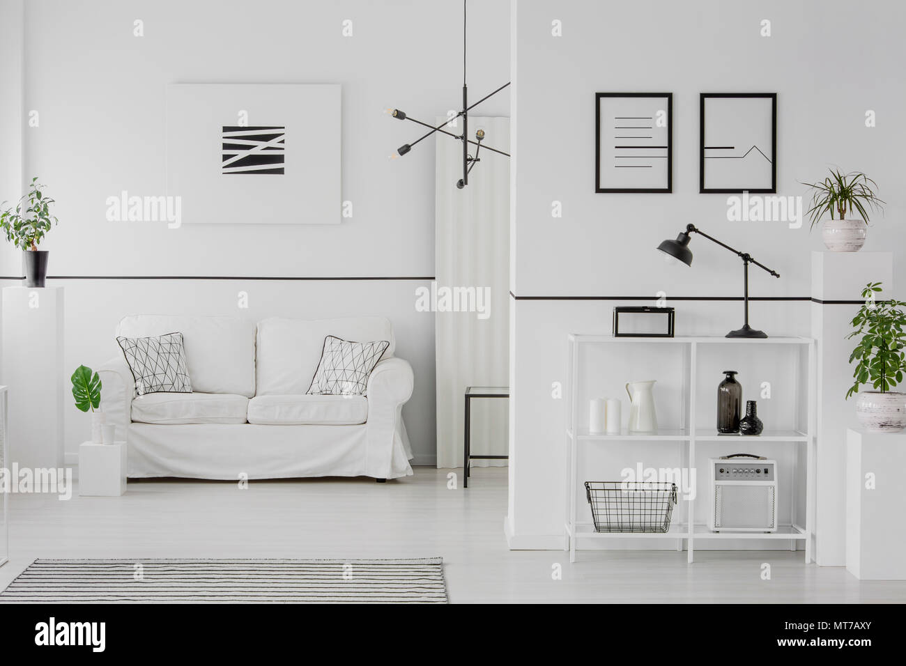 Black and white living room interior with comfy sofa, patterned pillows, simple posters and green plants - Stock Image