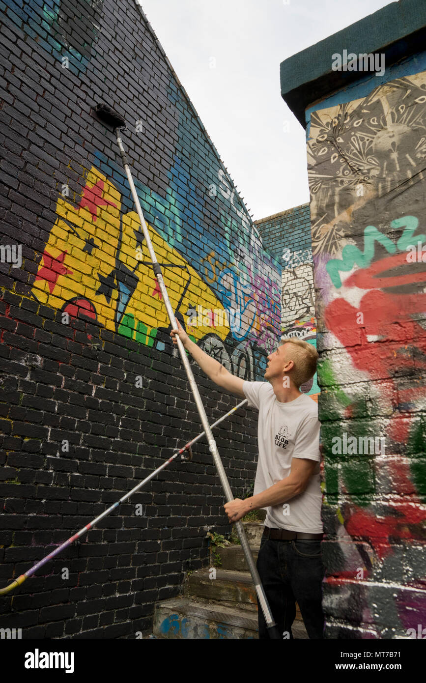 01c171666d8 Graffiti artist painting on walls of the Nomadic communal gardens space in  Shoreditch