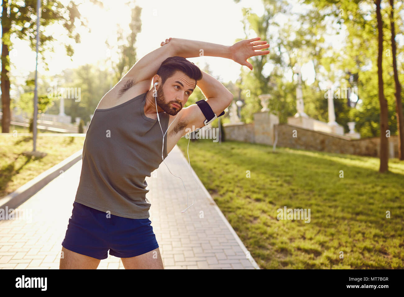 Young man doing stretching in the park. - Stock Image