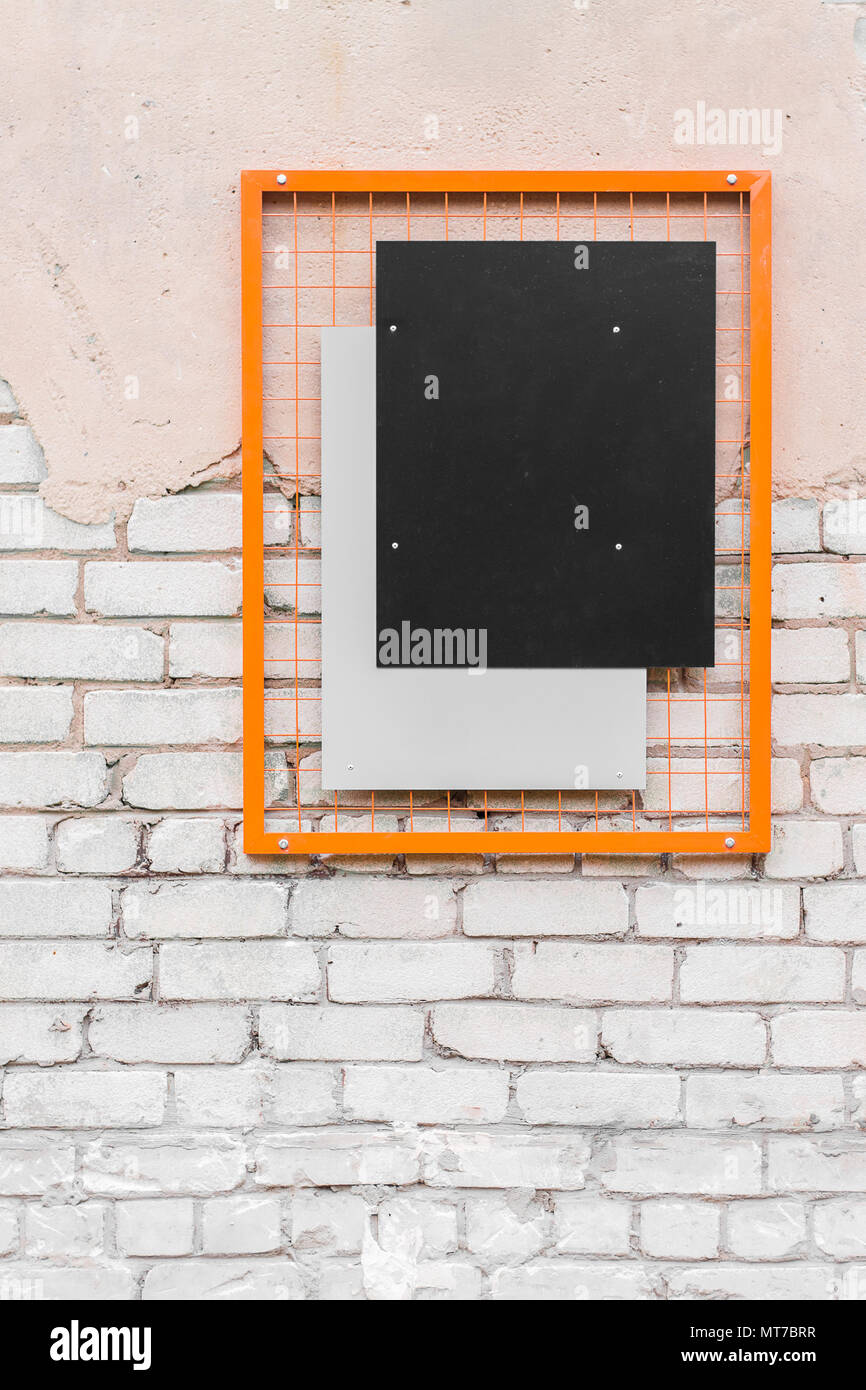 Blank black rectangle in an orange frame on a brick wall. Template ...
