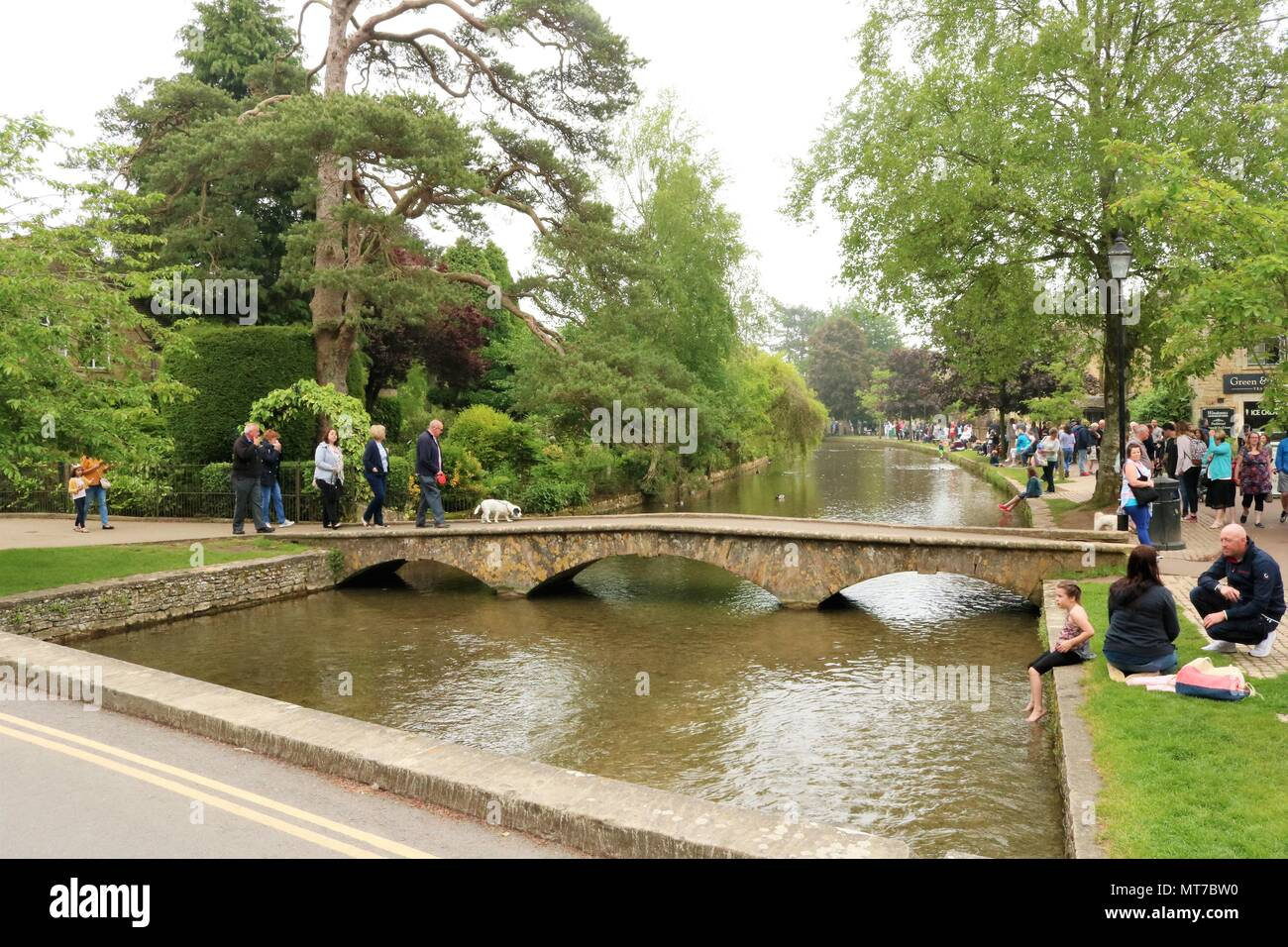 People enjoying the May Bank Holiday at Bourton on the Water, Gloucestershire, UK within the Cotswolds Area of Outstanding Natural Beauty - Stock Image