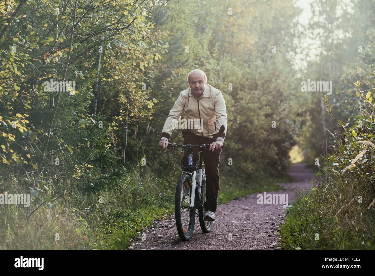 Portrait of man riding cycle in countryside. He is smiling a little - Stock Image