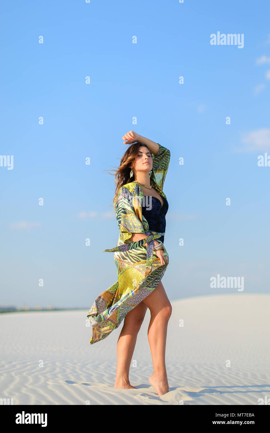 Young photo model wearing green beach robe and black swimsuit st - Stock Image