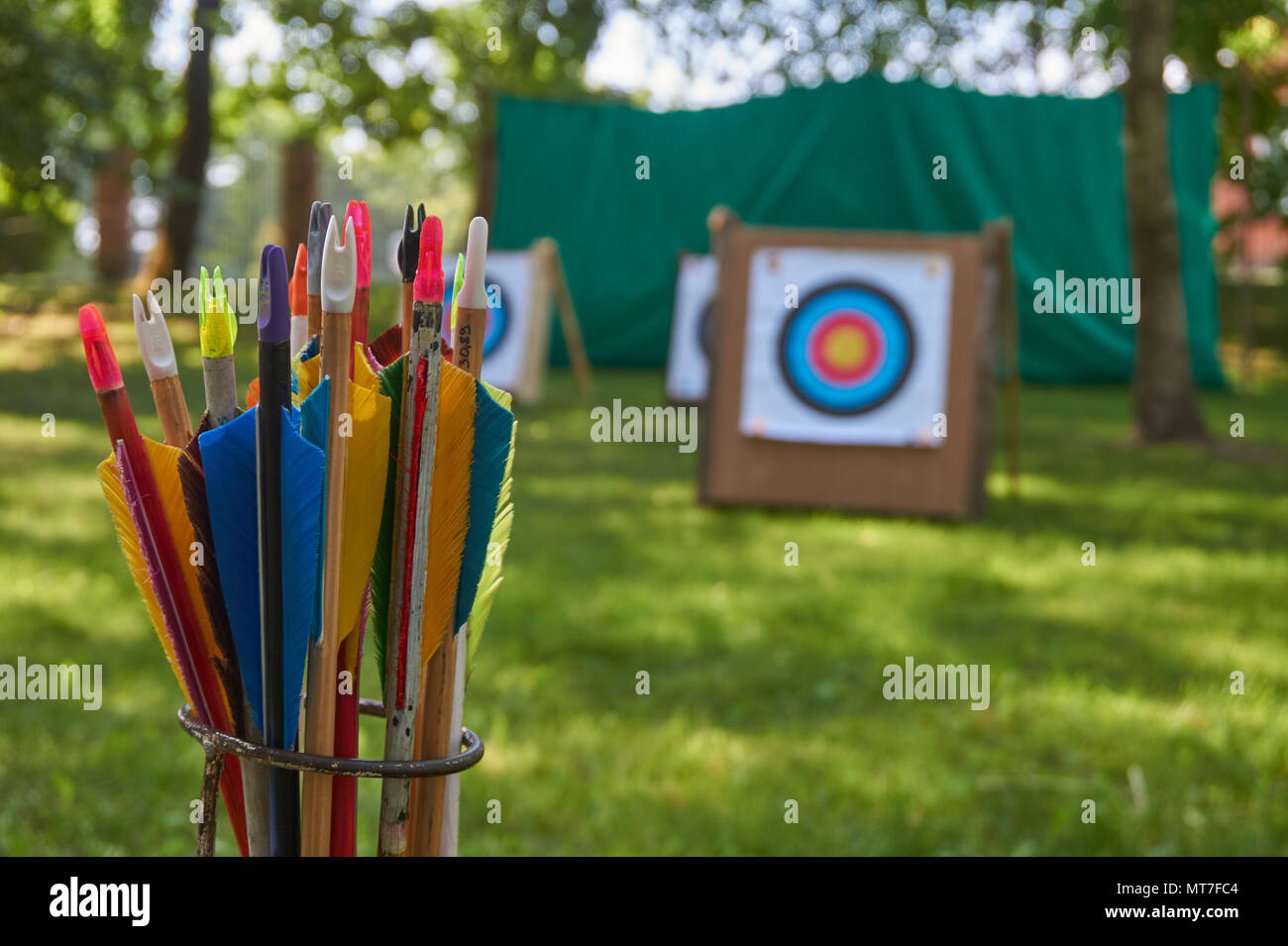 Aim concept with a low angle view across green grass of targets and a arrows in the foreground - Stock Image