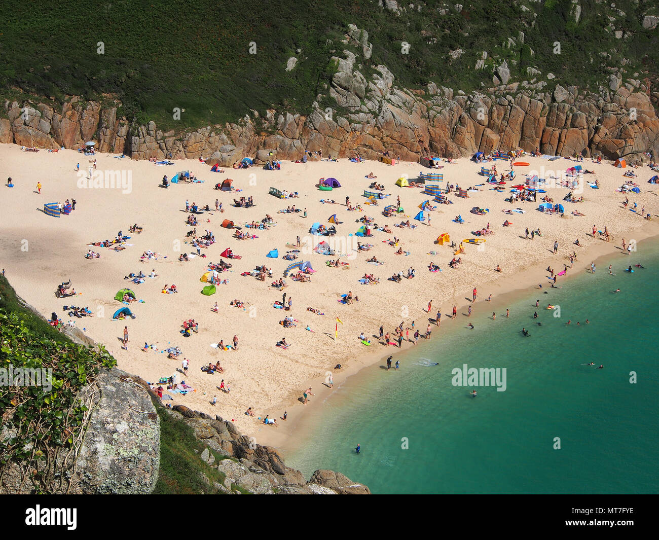 Beach at Pothcurno Bay / Cove in Cornwall, England, UK, showing the beach on a summer day. Aerial shot of holidaymakers sunbathing and swimming. Stock Photo