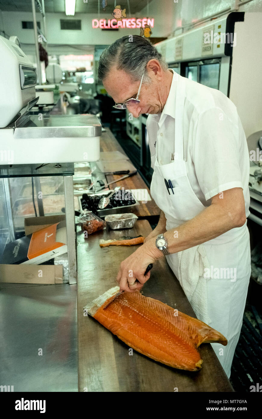 The owner of a Jewish delicatessen prepares smoked salmon to serve to his customers in the South Beach section of Miami Beach, Florida, USA. Ever since opening in the mid-1940s, The Delicacy Shop served as a neighborhood center for elderly New Yorkers who retired to the Sunshine State after World War II. That famous food store has since closed its doors, as have other historic delis like Wolfie's, Pumperniks, and the Rascal House. Their clientele of Jewish retirees left the South Beach area when the beachfront rooming houses where the old folks lived were converted to trendy boutique hotels. - Stock Image