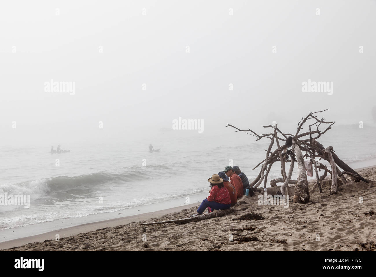 Family of four sitting by the ocean, California. - Stock Image