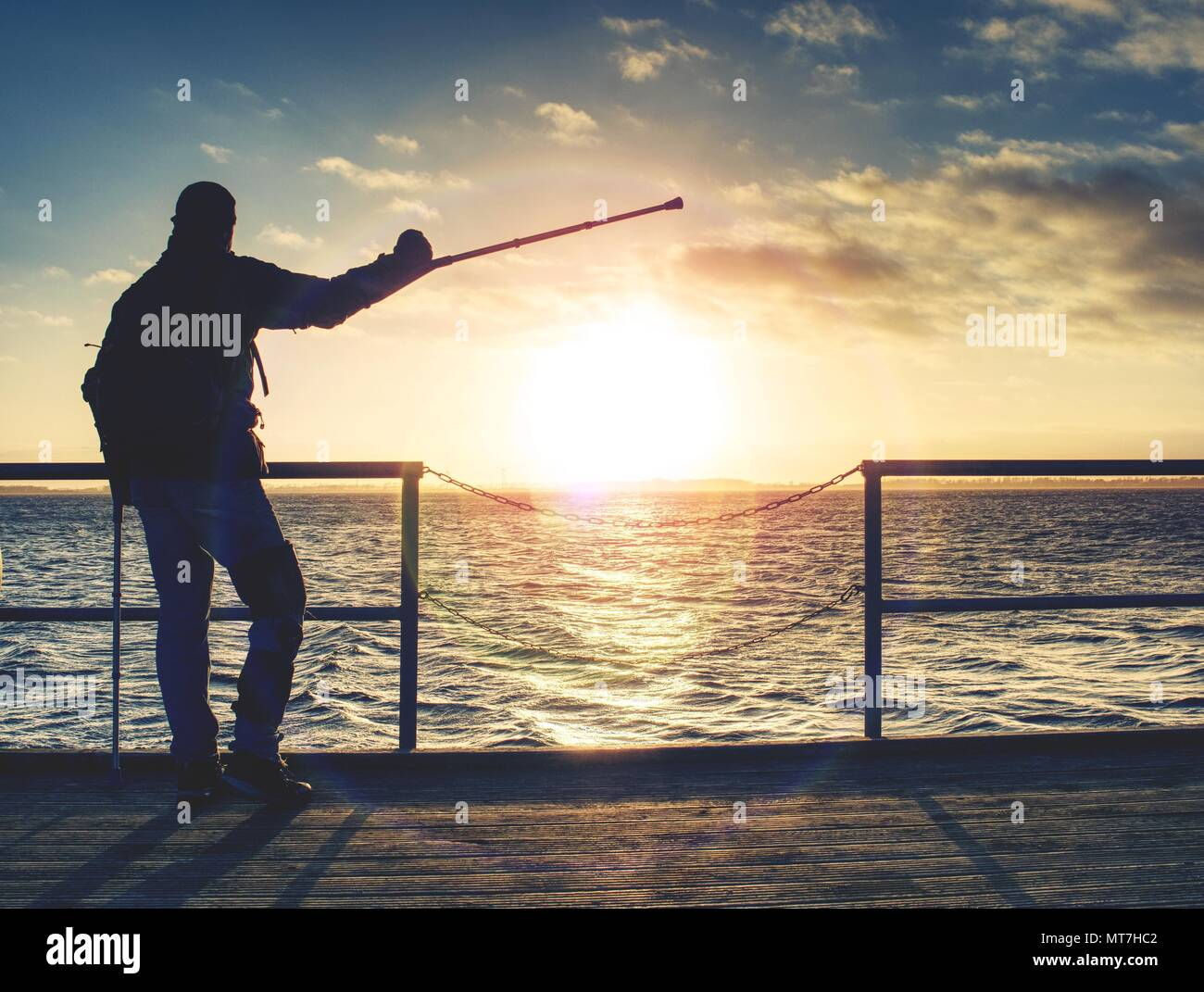 Disabled hurt hiker man is celebrate alone attachment of his target. Tourist stand or walk along on sea bridge within warm sunset, horizon where sky t - Stock Image