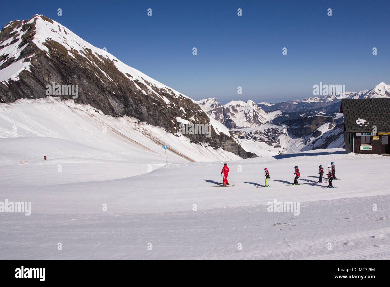 An instructor leads out a group of small children down a blue run in the ski resort of Avoriaz in the French Alps. The town can be seen at the bottom - Stock Image