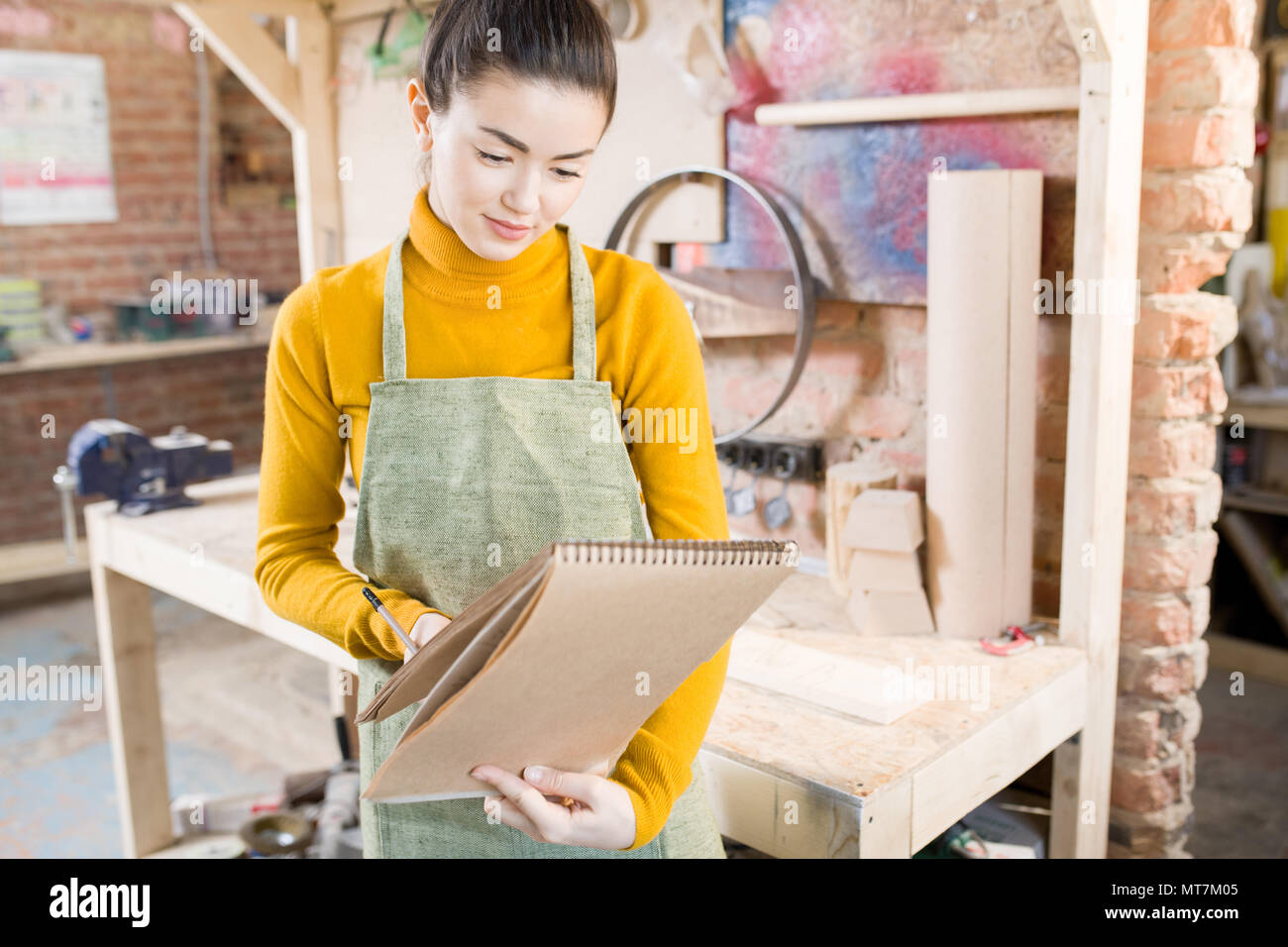 Smiling Female Artisan in Workshop - Stock Image
