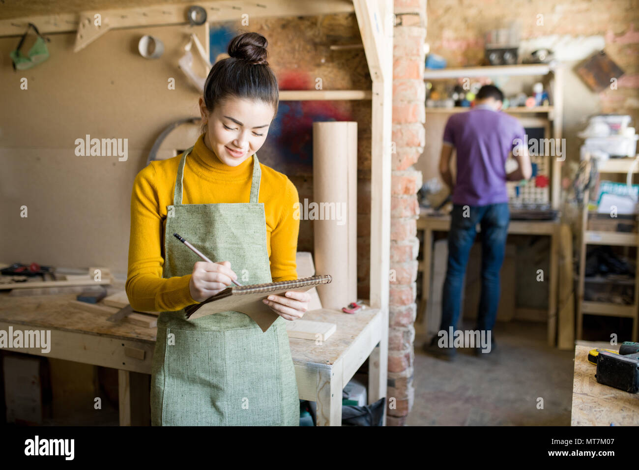 Cheerful Female Artisan in Workshop - Stock Image