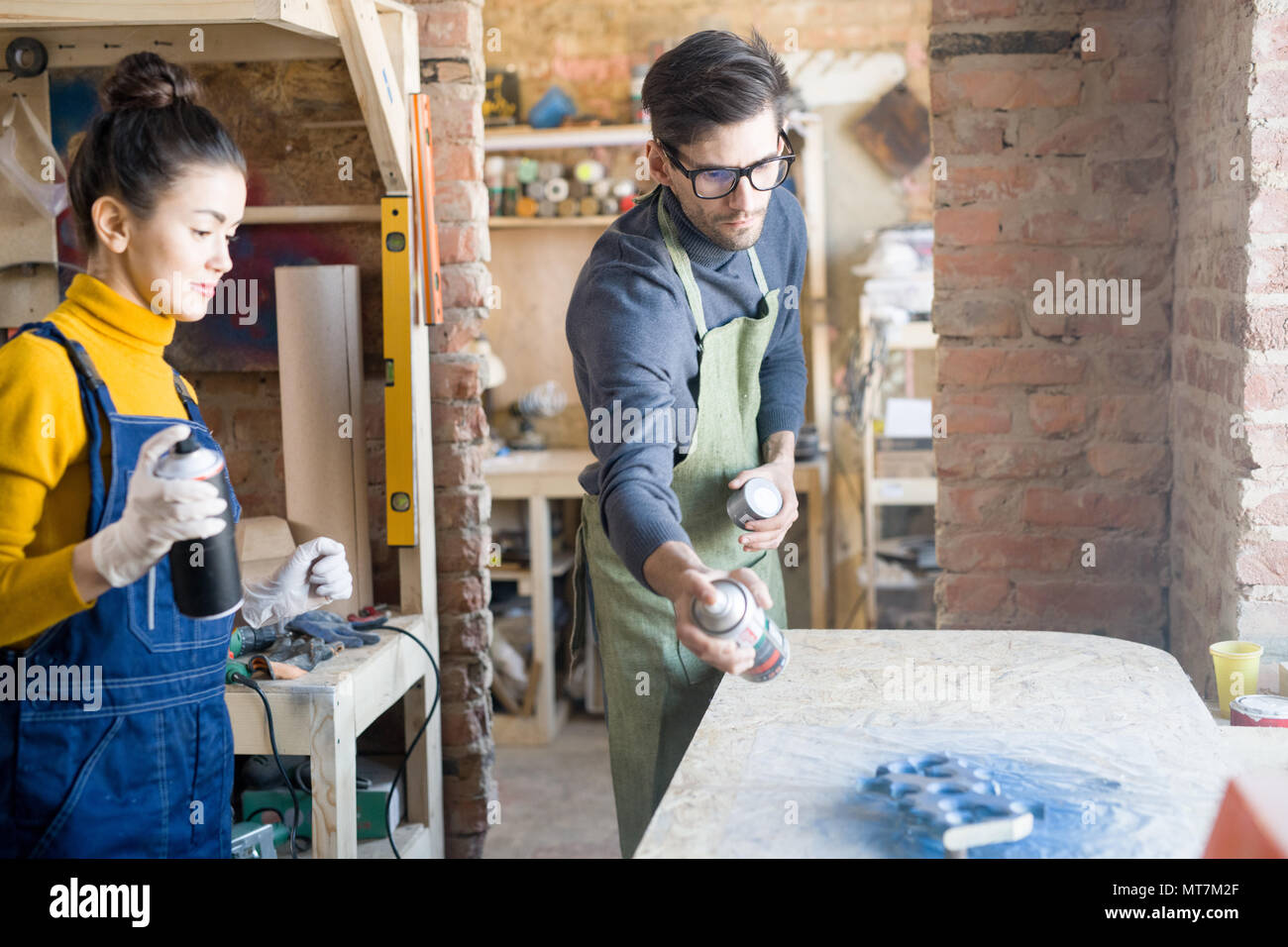 Two Artists Spray Painting Wood - Stock Image