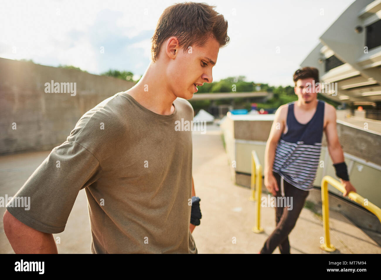 Teenage free runners preparing to do parkour on metal structure - Stock Image